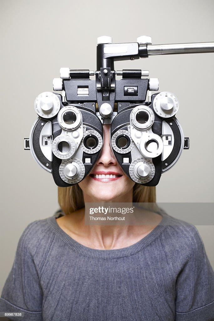 Mature woman looking through phoroptor : Stock Photo