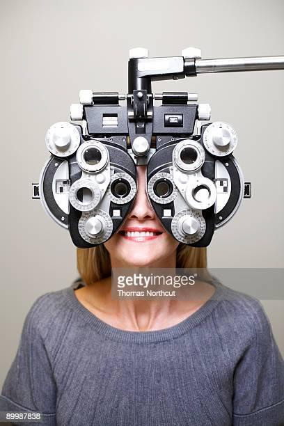 Mature woman looking through phoroptor