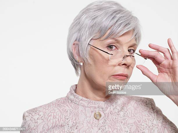 Mature woman lowering glasses, portrait, close-up