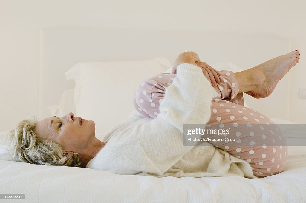mature woman lying on bed in fetal position stock photo getty images. Black Bedroom Furniture Sets. Home Design Ideas