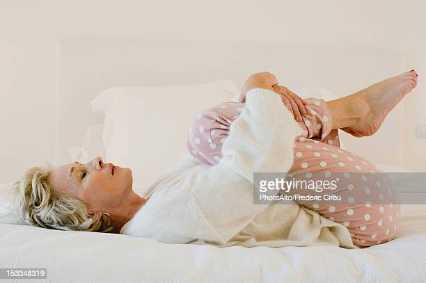 Mature woman lying on bed in fetal position