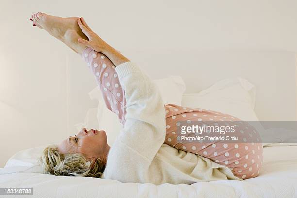 Mature woman lying on bed stretching legs
