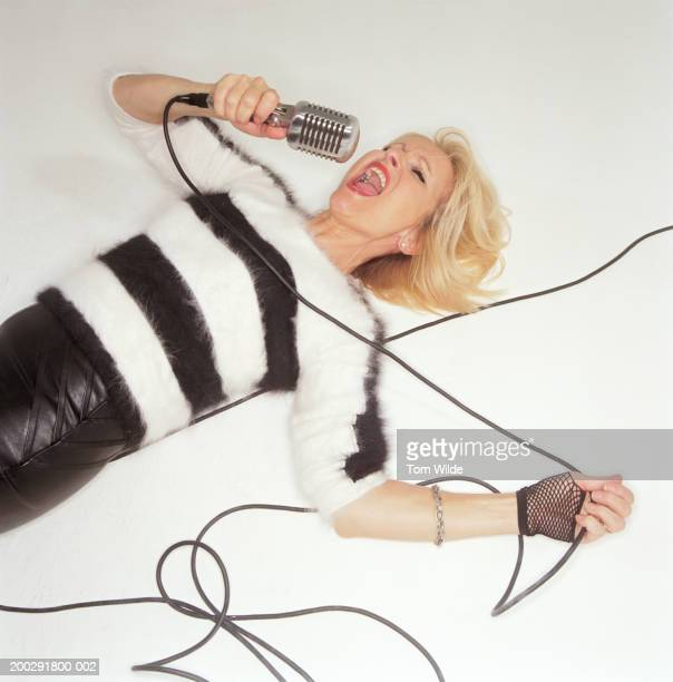 Mature woman lying on floor singing into microphone