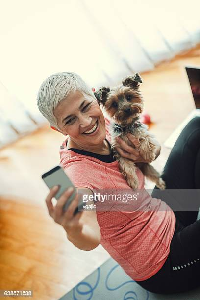 Mature Woman Making Selfie With Her Dog At Home.