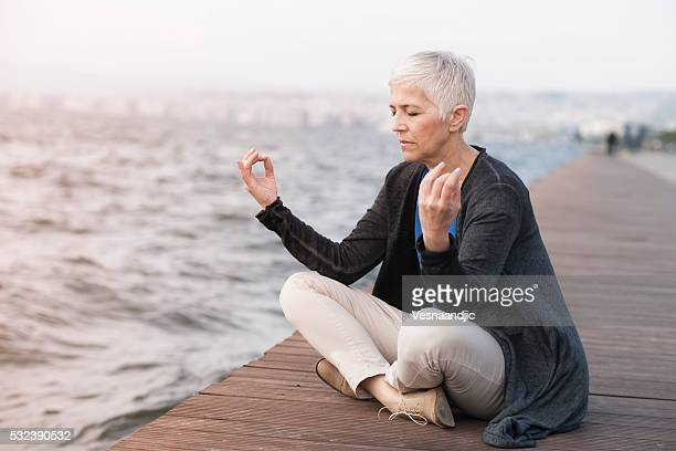Mature woman meditating near sea