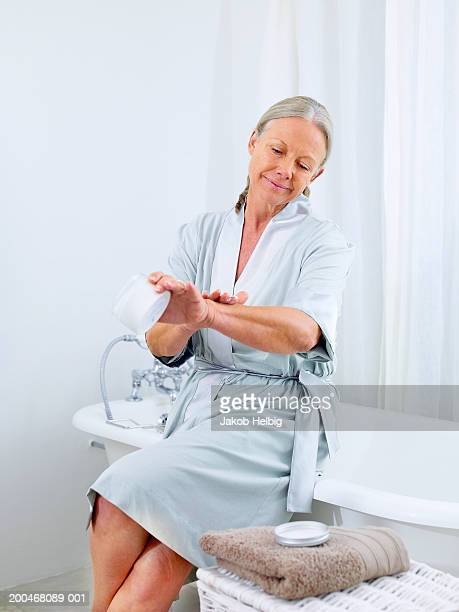 Mature woman moisturizing arms in bathroom