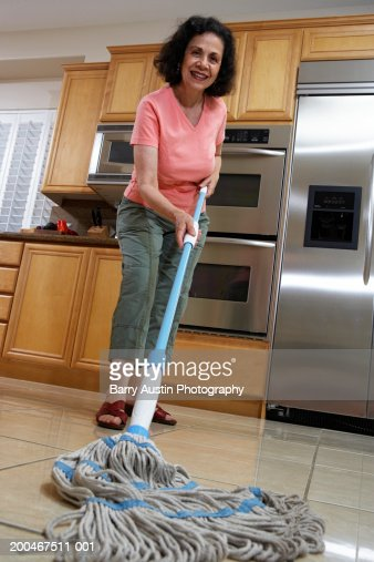 young woman cleaning kitchen floor elevated view stock photo