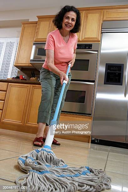 Mature woman mopping kitchen floor, smiling, portrait, low angle view
