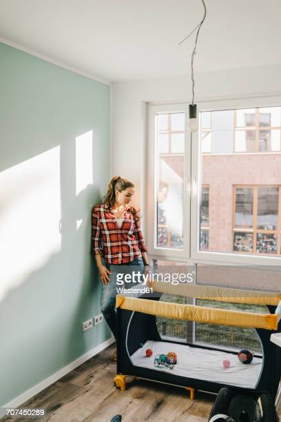 Mature woman moving house, looking at baby cot