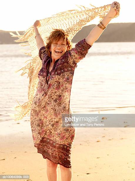Mature woman on beach holding flowing scarf over head