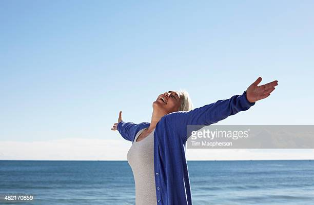 Mature woman on beach with arms outspread