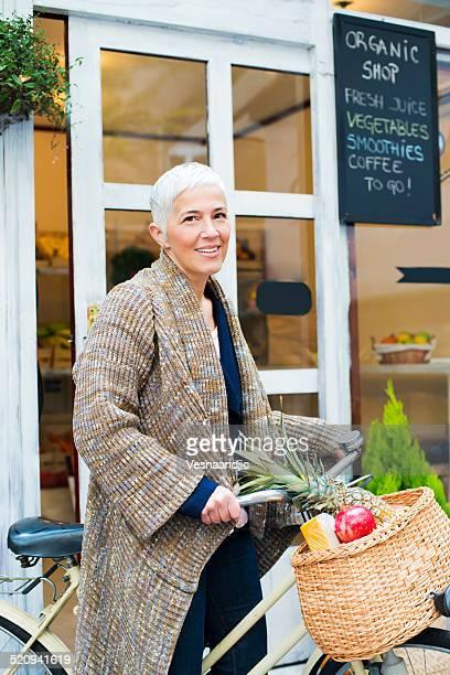 Ältere Frau auf Fahrrad vor Markt