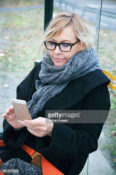 Mature woman on bus stop using cell phone