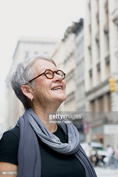 Mature Woman on City Sidewalk Looking Up