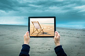 Mature woman on cloudy beach, holding digital tablet showing sunny beach scene, focus on hands and laptop