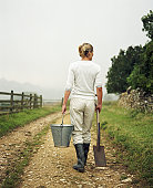 Mature woman on country lane carrying bucket and spade, rear view