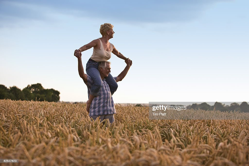 Mature woman on man's shoulders in wheat field.