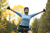 Mature woman on mountain bike at sunset, arms raised, looking up