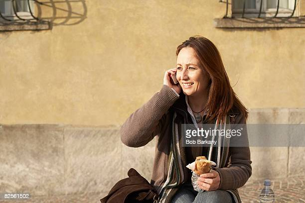 Mature woman on phone eating sandwich