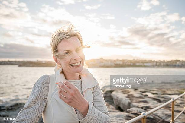 Mature woman on vacation smiling to camera, Bondi Beach