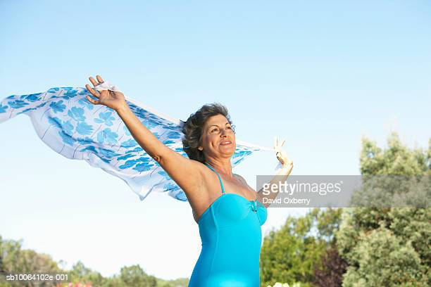 Mature woman outdoors, holding sarong in wind