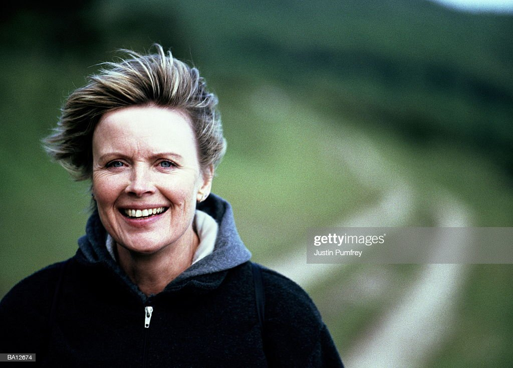 Mature woman outdoors smiling, hair blown back from face, portrait : Stock Photo