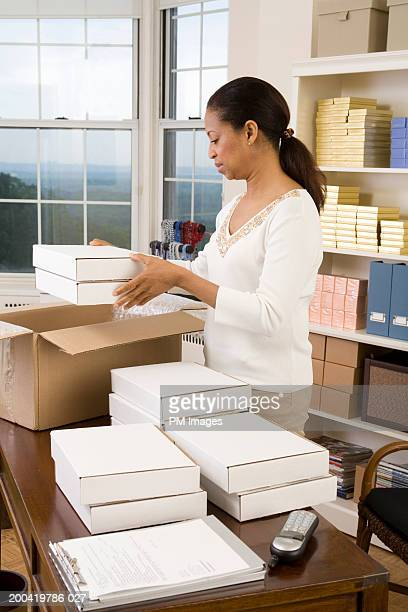 Mature woman packaging jewelry boxes in home office