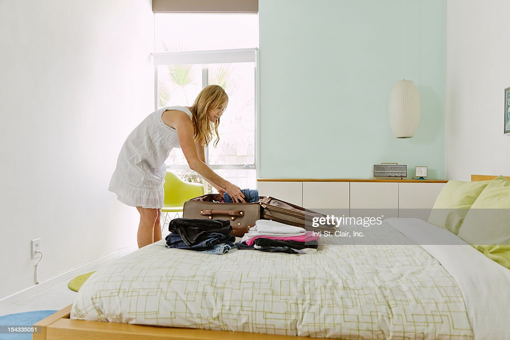Mature woman packing suitcase
