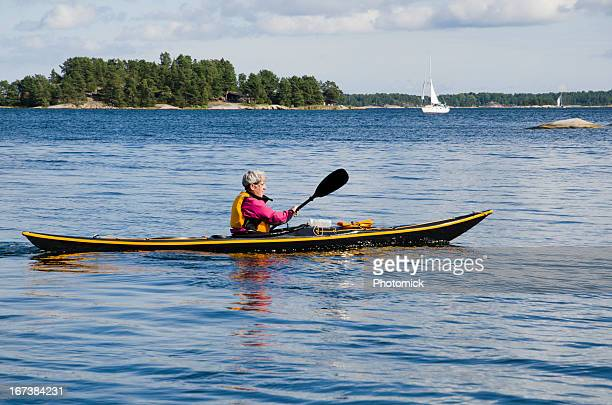 Mature woman paddling a black sea kayak