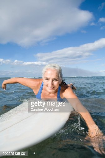 Mature woman paddling surfboard, smiling