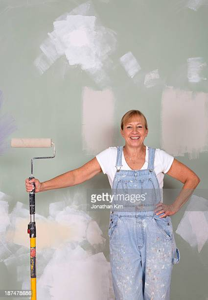 Mature woman painting her house.