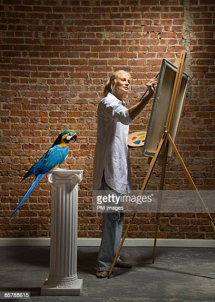 Mature Woman painting macaw