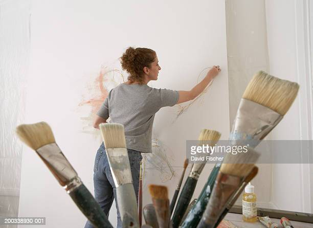 Mature woman painting on canvas, paintbrushes in foreground