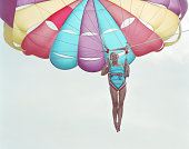 Mature woman parascending, wearing swimsuit, laughing, low angle view