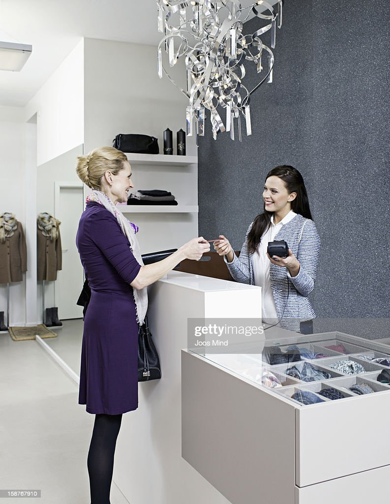 mature woman paying with credit card : Bildbanksbilder