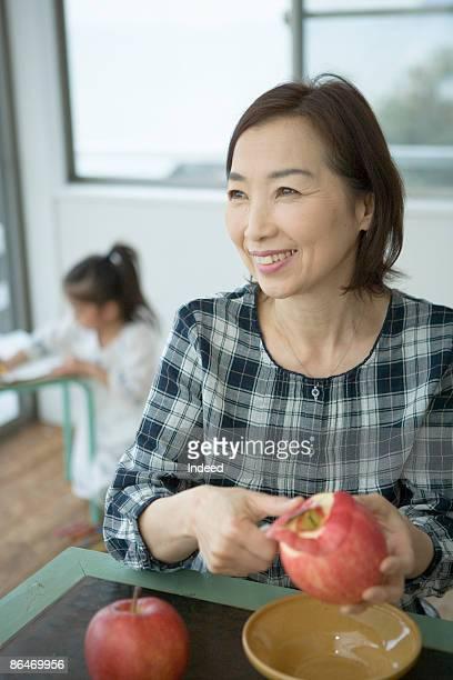 Mature woman peeling apple, girl in behind
