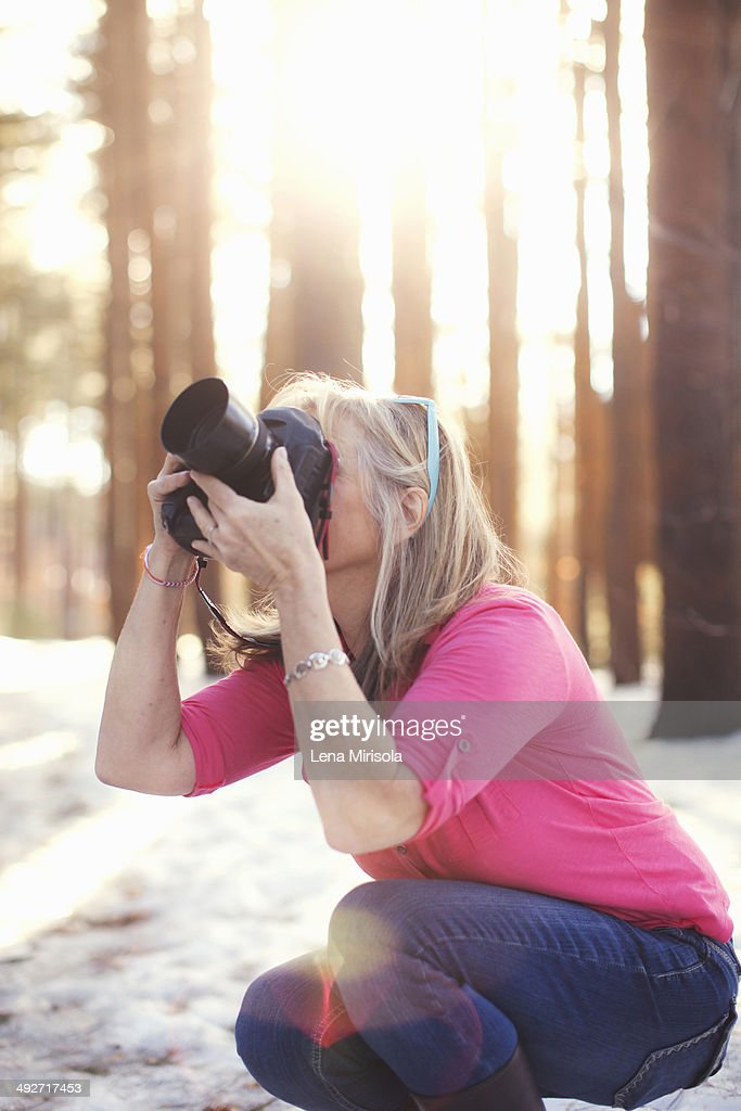 Mature woman photographing in forest : Stock Photo