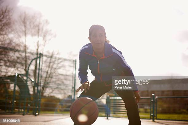 Mature woman playing basketball in park