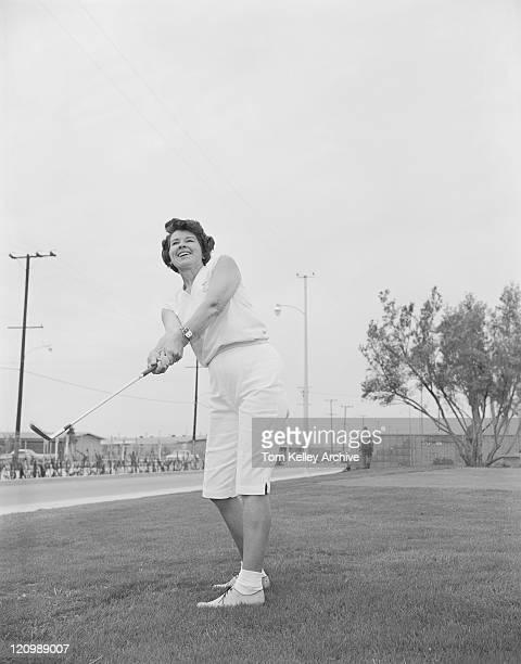 熟年女性のゴルフコースでのゴルフ