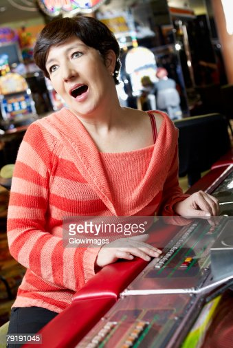 Mature woman playing on a slot machine and looking surprised : Foto de stock