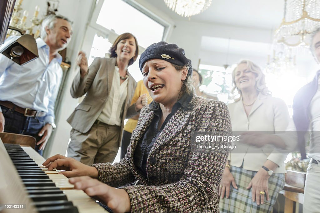 Mature woman playing Piano while friend listen : Stock Photo