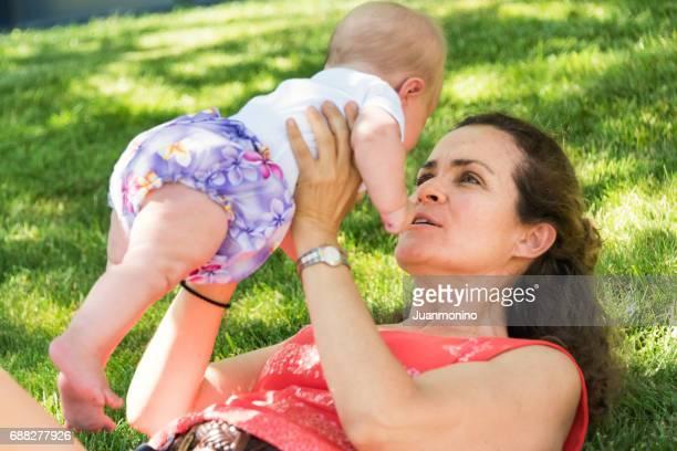 Reife Frau mit ihrem Baby spielen