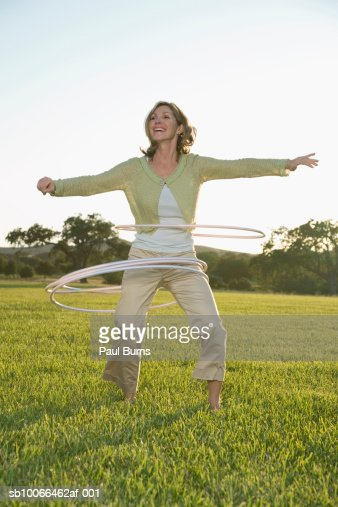 Mature woman playing with hula hoops on grass