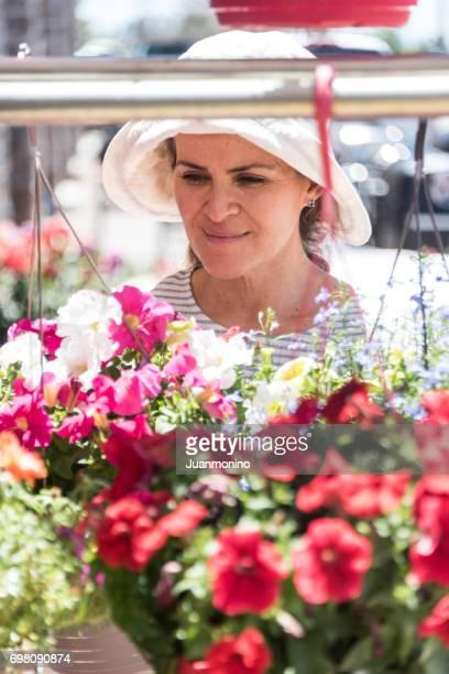 Reife Frau posiert in einem Blumenladen