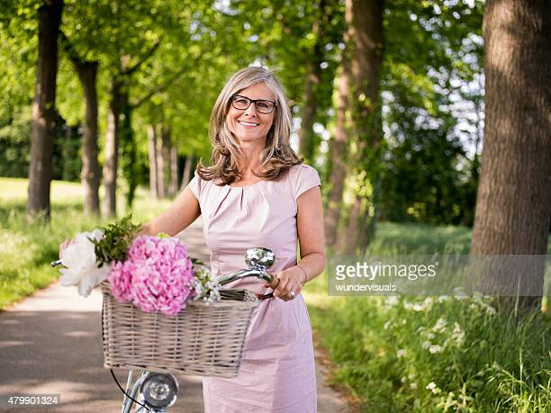 Mature woman posing with a classic bicycle in a park