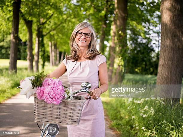 Reife Frau posieren mit einem klassischen Fahrrad in einem park