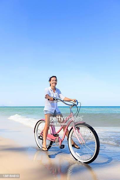 Mature Woman posing with bike on beach