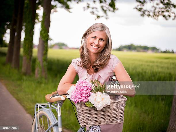 Mature woman posing with her vintage bicycle and flowers