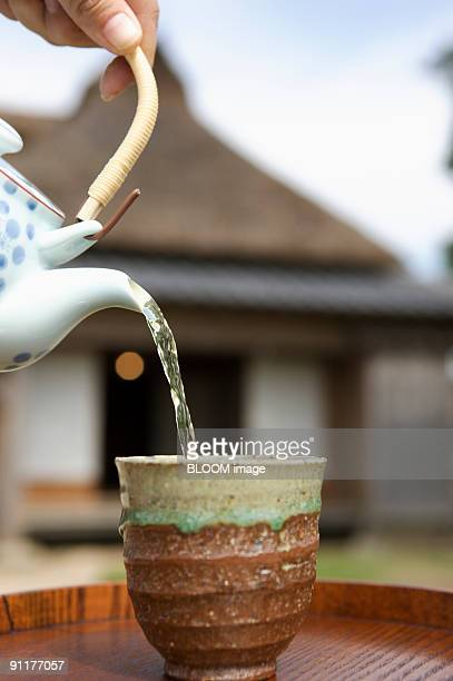 Mature woman pouring Japanese tea into cup, close-up of hand