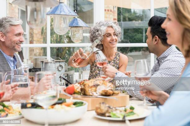 Mature woman pouring wine at dinner table with friends